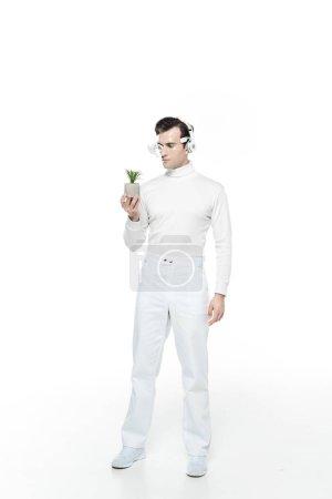 Photo pour Cyborg dans les écouteurs et lentille numérique des yeux regardant la plante en pot sur fond blanc - image libre de droit