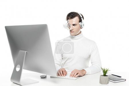 Cyborg in eye lens and headphones using computer near plant and notebook isolated on white