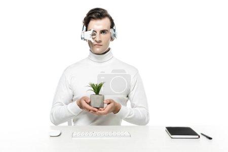 Photo pour Cyborg dans casque et lentille oculaire tenant usine près de souris d'ordinateur, clavier et ordinateur portable isolé sur blanc - image libre de droit
