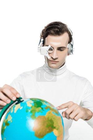 Photo pour Cyborg homme en lentille oculaire et écouteurs pointant vers le globe sur l'avant-plan flou isolé sur blanc - image libre de droit