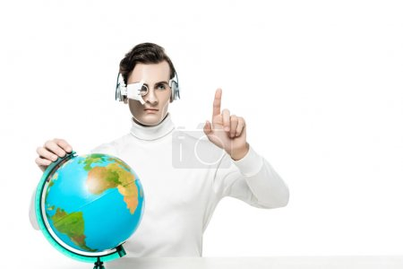 Cyborg in digital eye lens and headphones pointing with finger near globe isolated on white