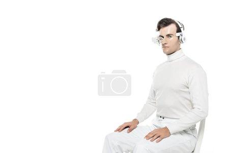 Photo pour Cyborg homme en casque et lentille oculaire regardant la caméra tout en étant assis sur une chaise isolée sur blanc - image libre de droit