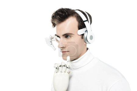 Photo pour Cyborg avec écouteurs, lentille numérique pour les yeux et main artificielle regardant loin isolé sur blanc - image libre de droit