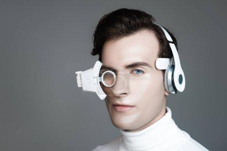 Cyborg dans les écouteurs et lentille oculaire en regardant la caméra isolée sur gris