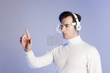 Cyborg in eye lens and headphones touching something isolated on purple
