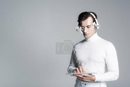 Cyborg hombre en auriculares con teclado de ordenador aislado en gris con espacio de copia