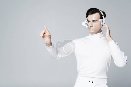 Cyborg man in headphones touching something and looking away isolated on grey