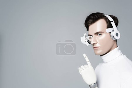 Cyborg man in headphones with artificial hand pointing with finger isolated on grey
