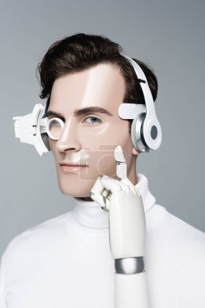 Cyborg in headphones with artificial hand looking at camera isolated on grey