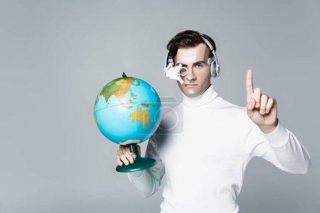 Photo pour Cyborg dans casque tenant globe tout en pointant vers le haut avec le doigt isolé sur gris - image libre de droit