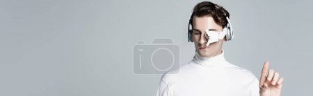 Cyborg man in headphones pointing with finger up isolated on grey, banner