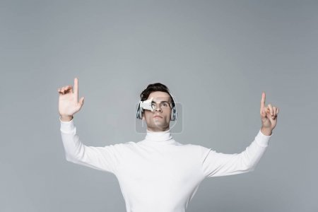 Brunette cyborg man in digital eye lens and headphones looking away while using something isolated on grey