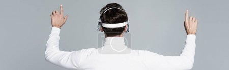 Back view of cyborg in headphones touching something isolated on grey, banner