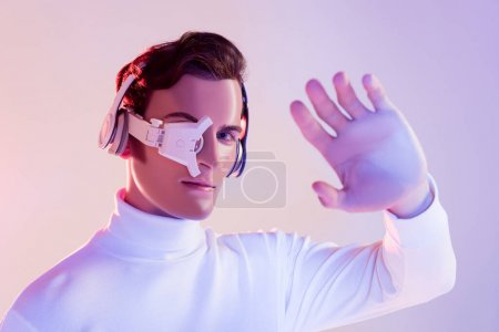 Photo for Cyborg in digital eye lens and headphones looking at camera near hand on blurred foreground on purple background - Royalty Free Image