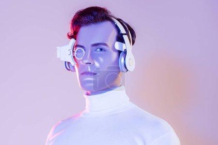 Cyborg homme en casque et lentille numérique des yeux regardant l'appareil photo sur fond violet