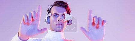 Cyborg homme en lentille numérique des yeux et écouteurs en utilisant quelque chose sur le premier plan flou sur fond violet, bannière
