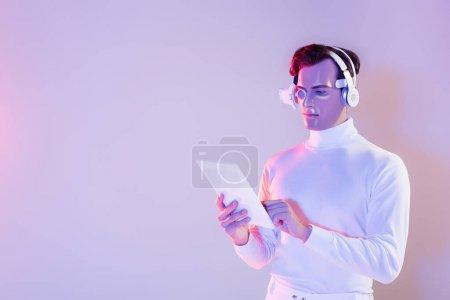 Photo pour Cyborg dans les écouteurs et lentille oculaire à l'aide d'une tablette numérique sur fond violet - image libre de droit