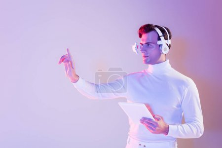 Cyborg in headphones holding digital tablet and using something on purple background