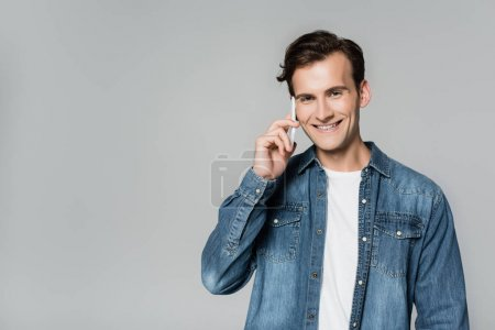 Positive man smiling at camera while talking on smartphone isolated on grey