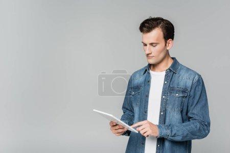 Photo pour Jeune homme veste en denim utilisant tablette numérique isolé sur gris - image libre de droit