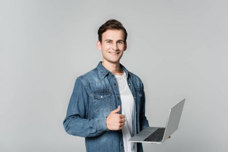 Smiling man showing thumb up while holding laptop isolated on grey