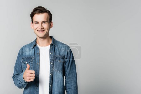 Photo for Smiling man in denim jacket showing thumb up isolated on grey - Royalty Free Image