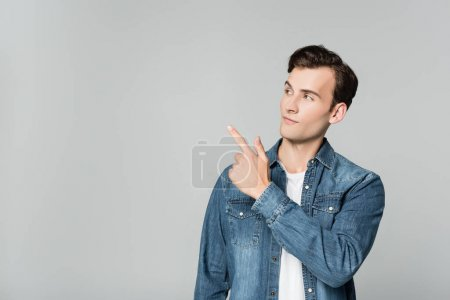 Photo for Young man in denim jacket pointing with finger isolated on grey - Royalty Free Image