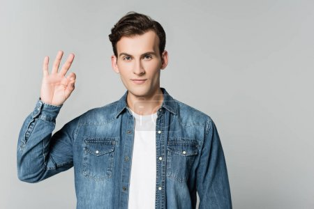 Photo for Brunette man in denim jacket showing ok gesture isolated on grey - Royalty Free Image