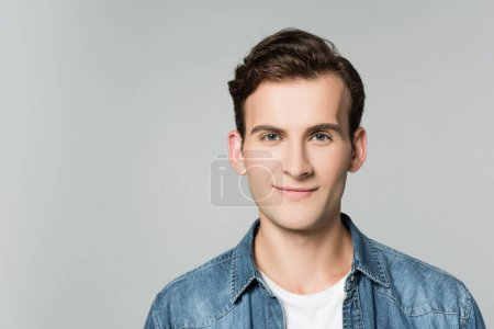 Brunette man in denim jacket smiling at camera isolated on grey