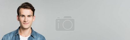 Young man smiling at camera isolated on grey, banner