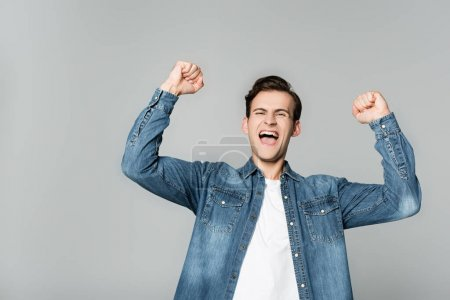Photo for Cheerful man showing yeah gesture isolated on grey - Royalty Free Image