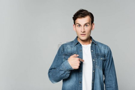 Young man in denim jacket pointing with finger on himself isolated on grey