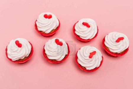 Draufsicht auf valentines Cupcakes mit rotem Herz auf rosa Hintergrund