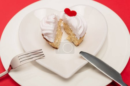 cupcake on plate with cutlery on red background