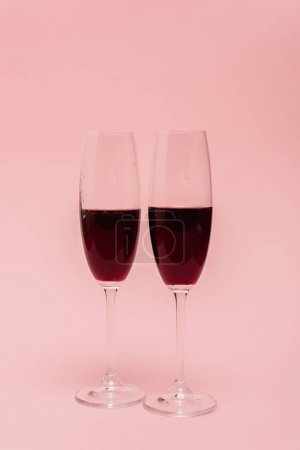 red wine in glasses isolated on pink