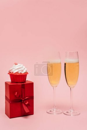 champagne glasses near gift and cupcake isolated on pink