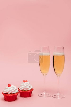 champagne glasses near cupcakes isolated on pink
