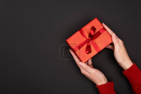 cropped view of woman holding red gift isolated on black