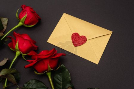 top view of roses and valentines envelope isolated on black