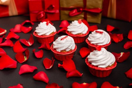 rose petals and valentines cupcakes isolated on black
