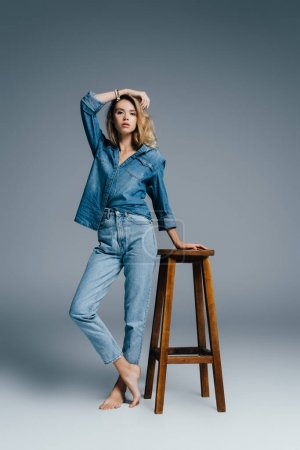 stylish barefoot woman in denim shirt and jeans leaning on high stool on grey