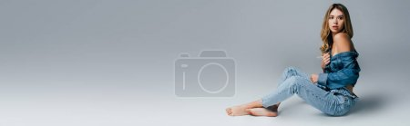 Photo for Seductive barefoot woman in unbuttoned denim clothes sitting on grey, banner - Royalty Free Image