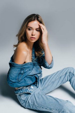 charming young woman in unbuttoned denim clothes touching forehead while sitting on grey
