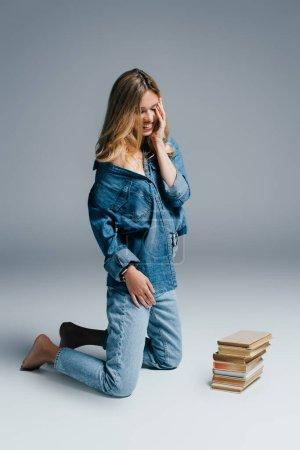 Lächelnde Frau in Jeanskleidung berührt Gesicht, während sie neben Büchern auf grau kniet
