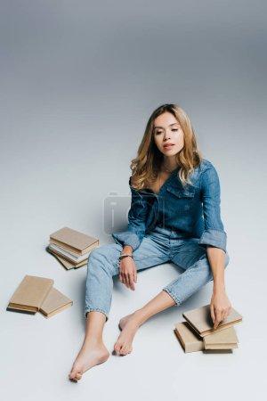 Photo pour Jeune femme pieds nus en denim chemise et jeans assis près de livres sur gris - image libre de droit