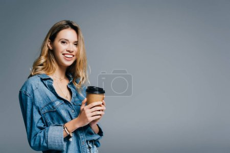 cheerful woman in denim shirt holding coffee to go and smiling at camera isolated on grey