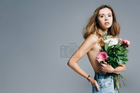 Photo for Sexy, topless woman with hand in back pocket of jeans holding bouquet isolated on grey - Royalty Free Image