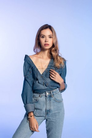 charming young woman in denim shirt and jeans looking at camera while standing isolated on blue