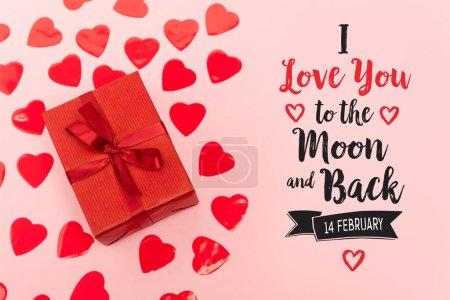 Photo pour Vue du haut des coeurs en papier rouge et boîte cadeau près de je t'aime à la lune et au dos, 14 février lettrage sur fond rose - image libre de droit