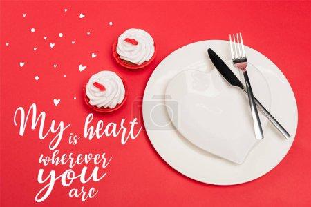 Draufsicht auf Cupcakes in der Nähe von Tellern mit Besteck und mein Herz ist überall, wo Sie Schriftzug auf rotem Hintergrund
